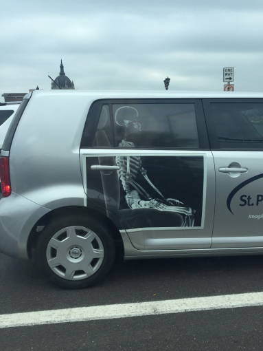 xray on the side of St. Paul Radiology vehicle--ironically (for a vehicle of a health care institution) the skeleton appears to have compression in lumbar spine and a possible impingement of the front of the hip socket. Maybe that's why it's hitching a ride to the clinic ...
